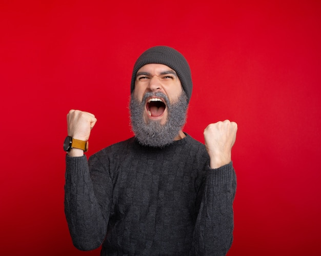 Chiuda sulla foto dell'uomo di grido che celebra sopra lo spazio rosso