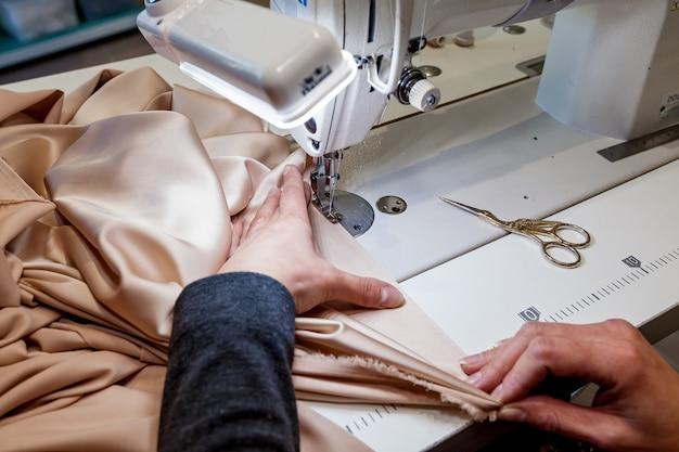 Foto ravvicinata del tessuto di cioccolato da cucire. la donna cuce il tessuto con una macchina da cucire