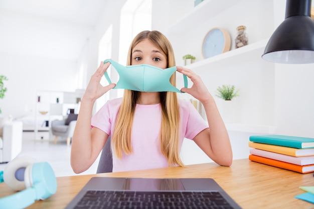 Foto ravvicinata di allievo scioccato bambino piccola ragazza seduta scrivania studio uso remoto laptop avere comunicazione online conversazione insegnante parlare parlare indossare maschera medica in casa al chiuso