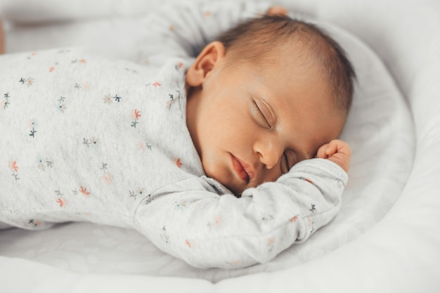 Primo piano foto di un bambino che dorme in abiti caldi con i capelli neri sentirsi al sicuro nel suo letto
