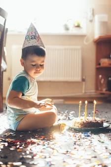 Chiuda sulla foto di un piccolo ragazzo caucasico che celebra il suo compleanno sul pavimento in posa con una torta e coriandoli mentre indossa un berretto da vacanza
