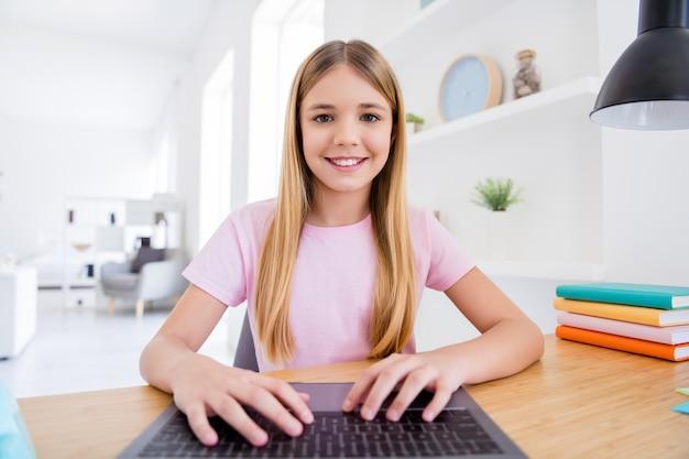 Foto ravvicinata di una bambina piccola che studia computer portatile per uso remoto e ha lezione di conversazione con insegnante online mandare sms con le mani tastiera sedersi comfort tavolo accogliente in casa al chiuso