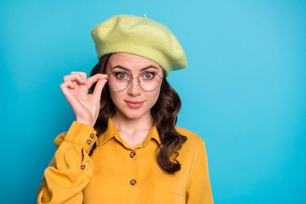 Foto ravvicinata di una bella ragazza carina e intelligente, che ha un bell'aspetto con gli occhiali impressionati dalla novità dell'affare isolata su uno sfondo di colore blu