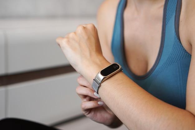 Foto ravvicinata della ragazza sportiva utilizzando fitness tracker o cardiofrequenzimetro