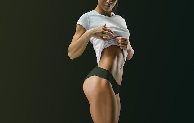 La foto del primo piano della donna forte mostra l'abbigliamento sportivo dell'addome muscolare. modello femminile fitness in posa su sfondo nero. bella donna con pelle pulita e luminosa isolata su sfondo scuro.