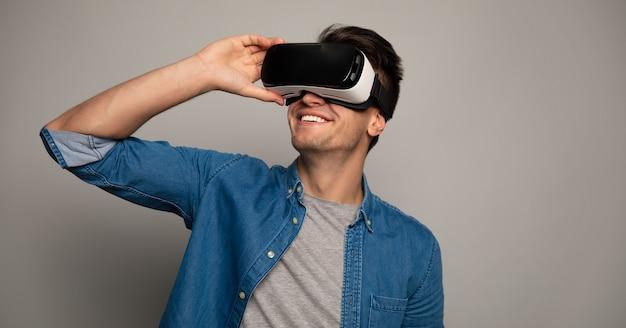 Foto ravvicinata di un uomo sorpreso con gli occhiali vr, che allarga le mani davanti alla telecamera.