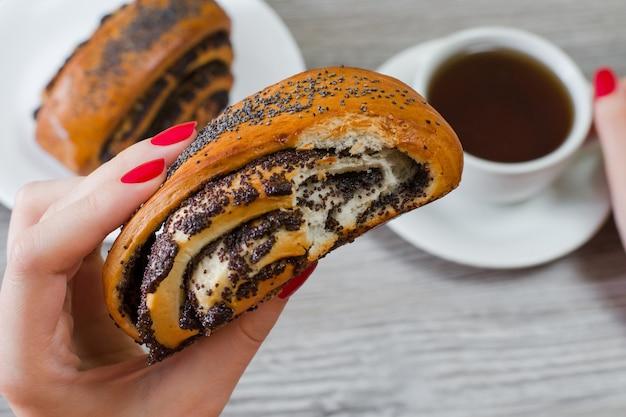 Foto ravvicinata di un gustoso panino ricco di semi di papavero, tazza di tè sullo sfondo