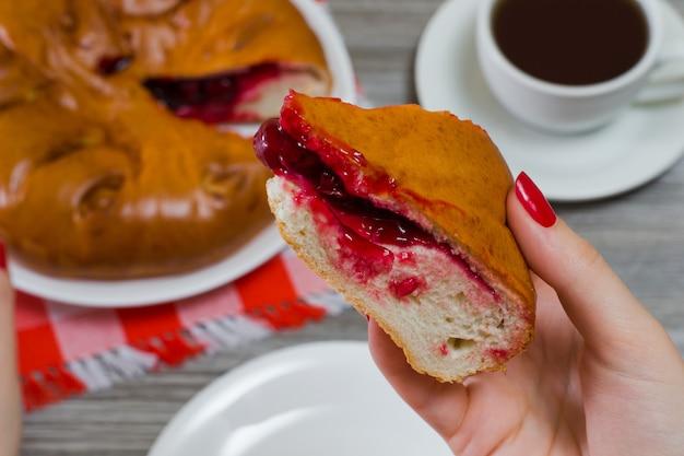 Foto ravvicinata di un gustoso pezzo di torta di ciliegie nella mano di una donna