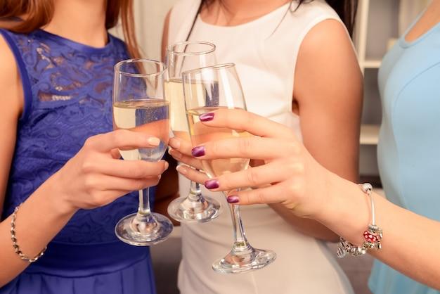 Primo piano foto di tre mani che sollevano bicchieri con shampagne in un pane tostato