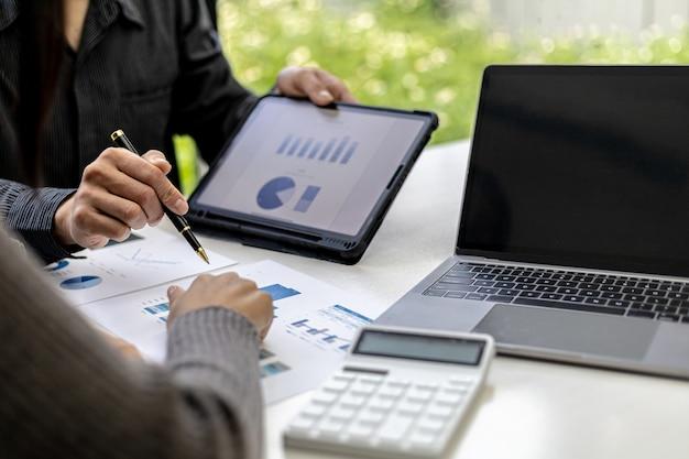 Foto ravvicinata di due uomini d'affari che puntano a una scheda dati di vendita in formato grafico, si incontrano sul tema della gestione della crescita delle vendite. concetto di cooperazione commerciale e gestione delle vendite.