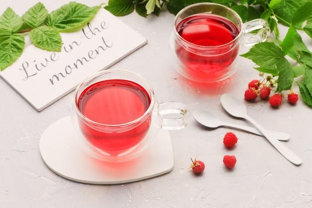 Foto del primo piano di due tazze del tè e dei lamponi fragranti della frutta su fondo bianco.