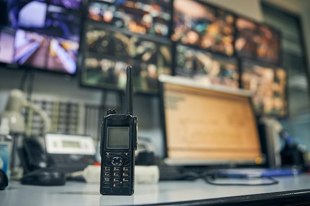 Foto ravvicinata di un walkie-talkie seduto su una scrivania in una sala di controllo della sicurezza