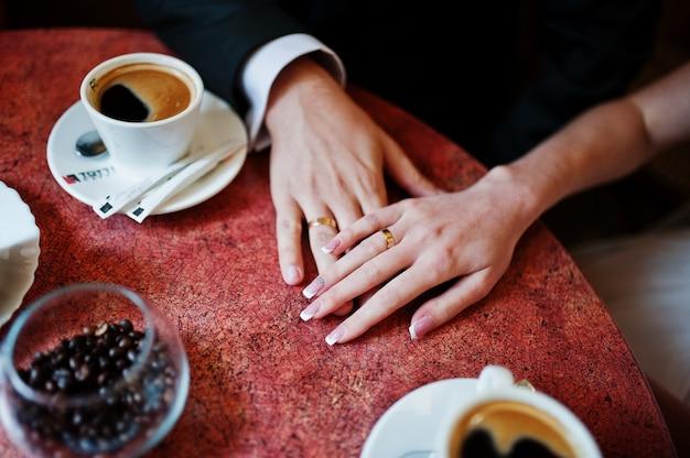 Foto del primo piano di una coppia di sposi che si tengono per mano in un piccolo caffè.