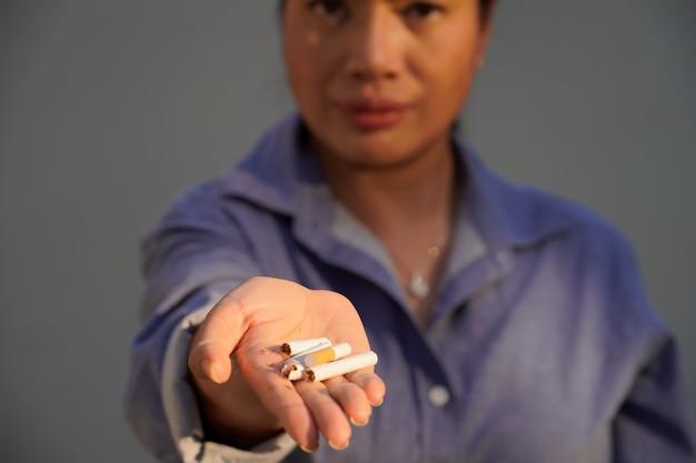 Foto ravvicinata di una donna che distrugge le sigarette, giornata mondiale senza tabacco, 31 maggio, smettere di fumare.