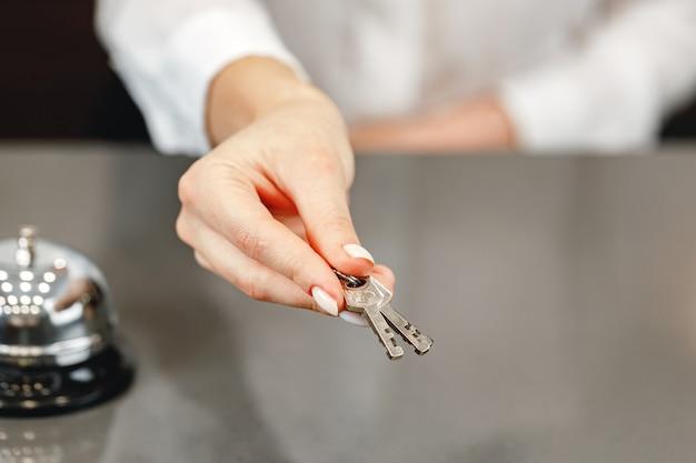 Close up foto di donna receptionist hotel dandovi la chiave della porta
