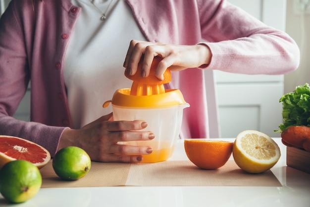 Primo piano foto di una donna che fa il succo a casa di frutta utilizzando uno spremiagrumi manuale