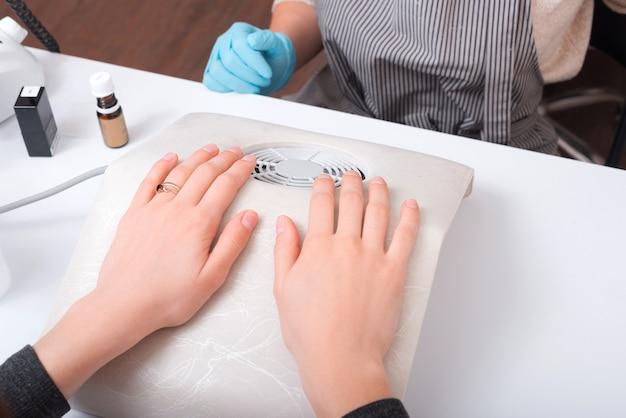 Primo piano foto di donna seduta alla procedura di chiodi davanti al maestro