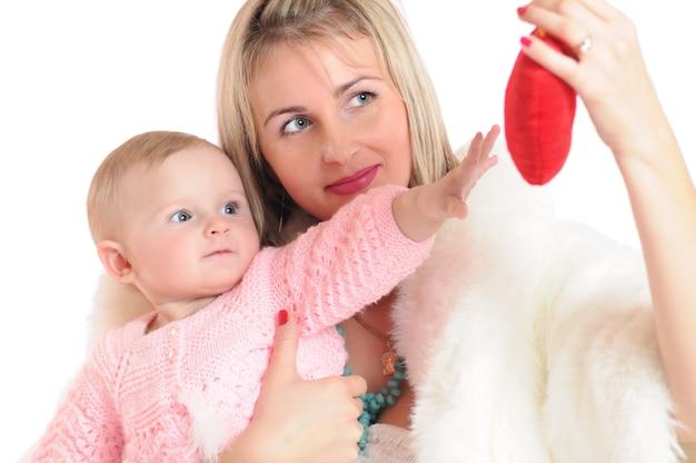 Foto del primo piano di una donna con bambino che guarda con interesse al giocattolo a forma di cuore rosso