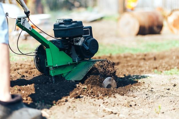 La foto vicina del giovane giardiniere dell'agricoltore coltiva il rototiller del suolo