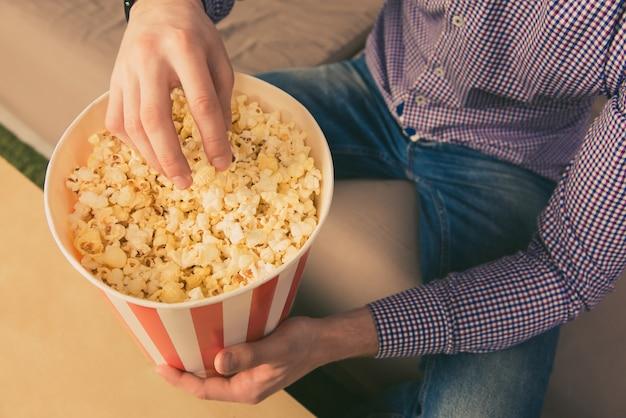 Close up foto di giovane uomo che mangia popcorn a casa