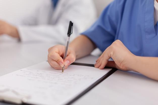 Primo piano della mano dell'infermiera della donna del medico che analizza l'esame di malattia che scrive perizia medica sulla lavagna per appunti che prescrive il trattamento del farmaco della pillola. lavoro di squadra specializzato che lavora nella sala riunioni