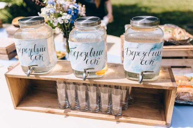 Primo piano della festa da picnic nel tavolo delle bevande del parco con una grande brocca e bottiglie di vetro riempite con limonata rosa ghiacciata e limoni freschi, paglia roteata rosa, cucchiai e segno sulla tovaglia a quadretti rosa