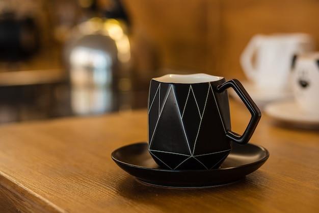 L'immagine ravvicinata della tazza di ceramica nera sul piatto nero è sul tavolo marrone