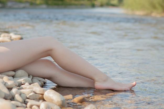 Immagine ravvicinata, gambe femminili sul fiume.