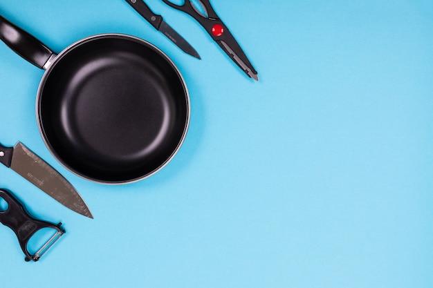 Chiuda sull'immagine del gruppo di utensili della cucina sul blu