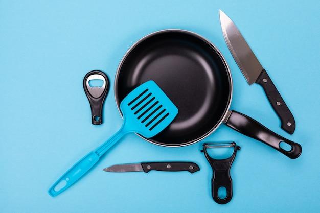 Chiuda sull'immagine del gruppo di utensili della cucina con copyspace sul blu