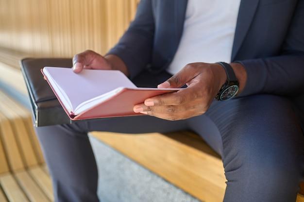 Immagine ravvicinata delle mani di un uomo che tengono un taccuino