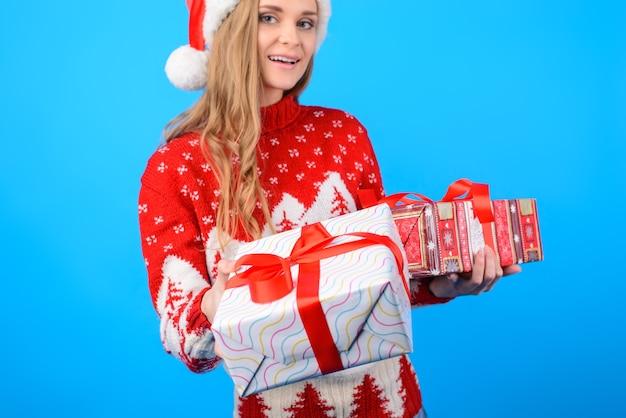 Chiuda sull'immagine della donna graziosa sorridente in maglione caldo lavorato a maglia sta dando una scatola attuale, fuoco selettivo, fondo isolato