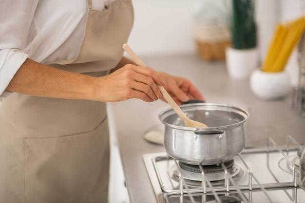 Primo piano immagine di una donna che mescola qualcosa in una salsiccia