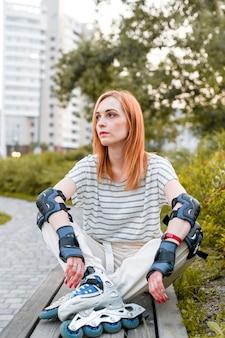 Immagine ravvicinata di giovane donna seduta su una panchina. abbigliamento protettivo per pattinaggio a rotelle