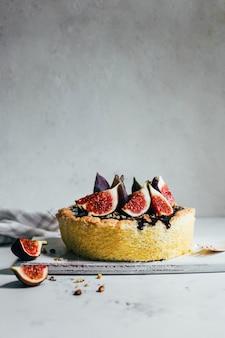 Primo piano di una torta con cioccolato e fichi su sfondo grigio