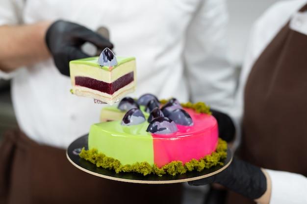 Primo piano di un pezzo di torta di mousse nelle mani di un pasticcere maschio.
