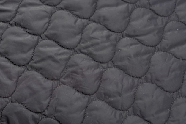 Primo piano di un pezzo di tessuto trapuntato, rivestimento della giacca.