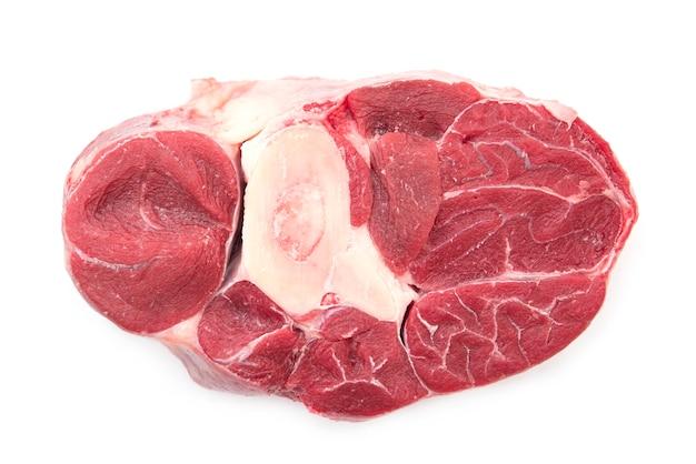 Primo piano pezzo di carne di manzo o vitello crudo con osso isolato su bianco, vista dall'alto