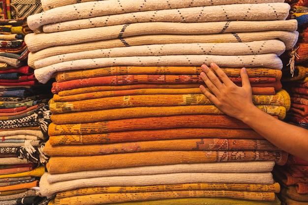 Chiuda in su del mucchio di tappeti colorati in un mercato in marocco