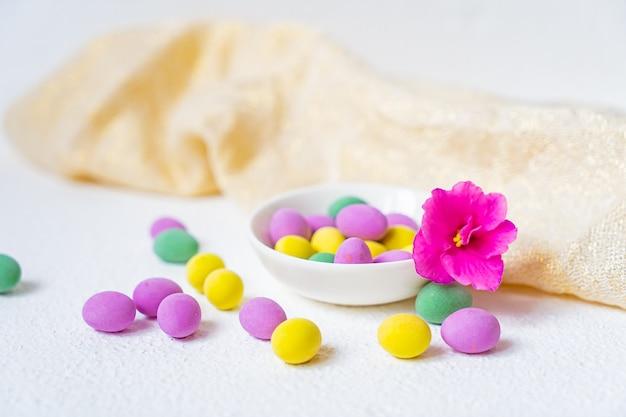 Primo piano di una pila di uova di pasqua di cioccolato colorate e un fiore rosa isolato su sfondo bianco