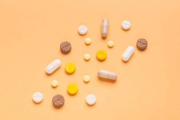 Primo piano di pillole su uno sfondo arancione il concetto di dipendenza da antidolorifici