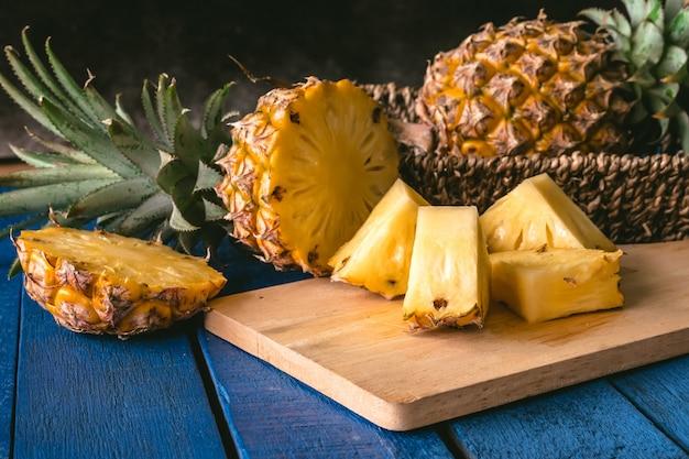 Chiuda in su della frutta dell'ananas con le fette sulla tabella di legno blu
