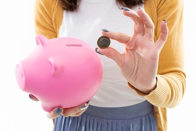 Primo piano di un salvadanaio rosa e una moneta nelle mani