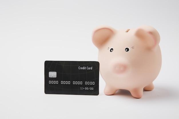 Chiuda in su della banca dei soldi piggy rosa e della carta di credito nera isolata sul fondo bianco della parete. accumulo di denaro, investimenti, servizi bancari o aziendali, concetto di ricchezza. copia spazio pubblicitario mock up.
