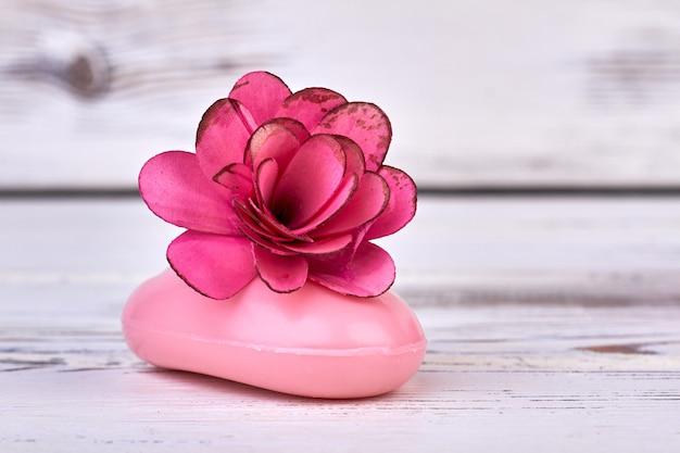 Sapone rosa del primo piano con la testa di fiore rosa su legno bianco.
