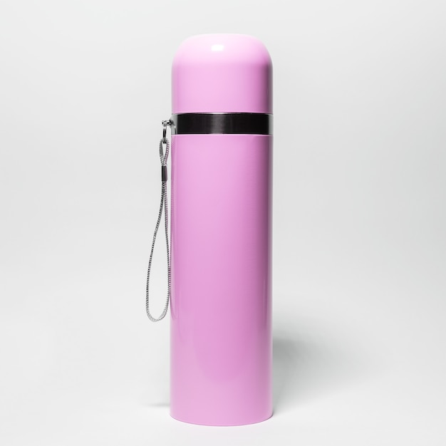 Close-up di thermos in acciaio inox rosa isolato su bianco.