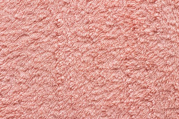 Trama di asciugamano rosa close-up. asciugamano di spugna. consistenza aumentata