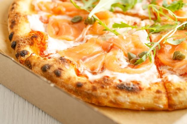 Primo piano di pizze con varietà di verdure e formaggio in cartone