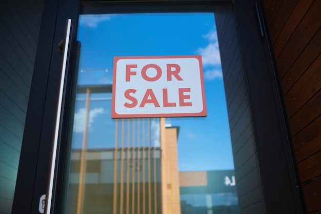 Primo piano del cartello in vendita appeso alla porta di vetro del nuovo edificio per uffici