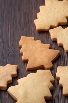 Chiuda su del biscotto dell'albero di natale del pan di zenzero di sapore normale sul fondo di legno della tavola. cibo per la celebrazione delle vacanze di natale.